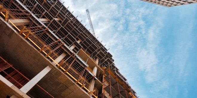 Building construction site with scaffolding gondola