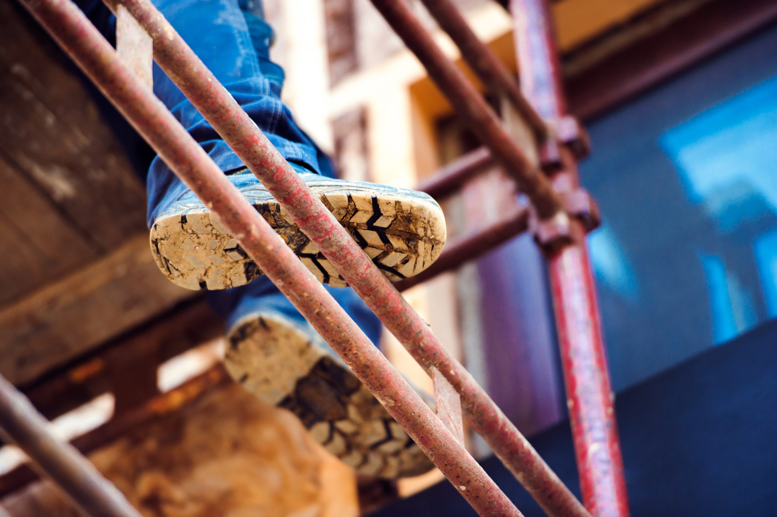 Detail of legs of construction worker standing on scaffolding